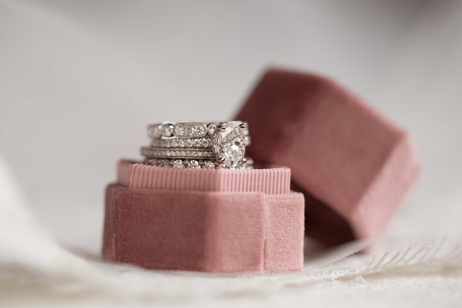 Stack of diamond rings in a mauve velvet ring box