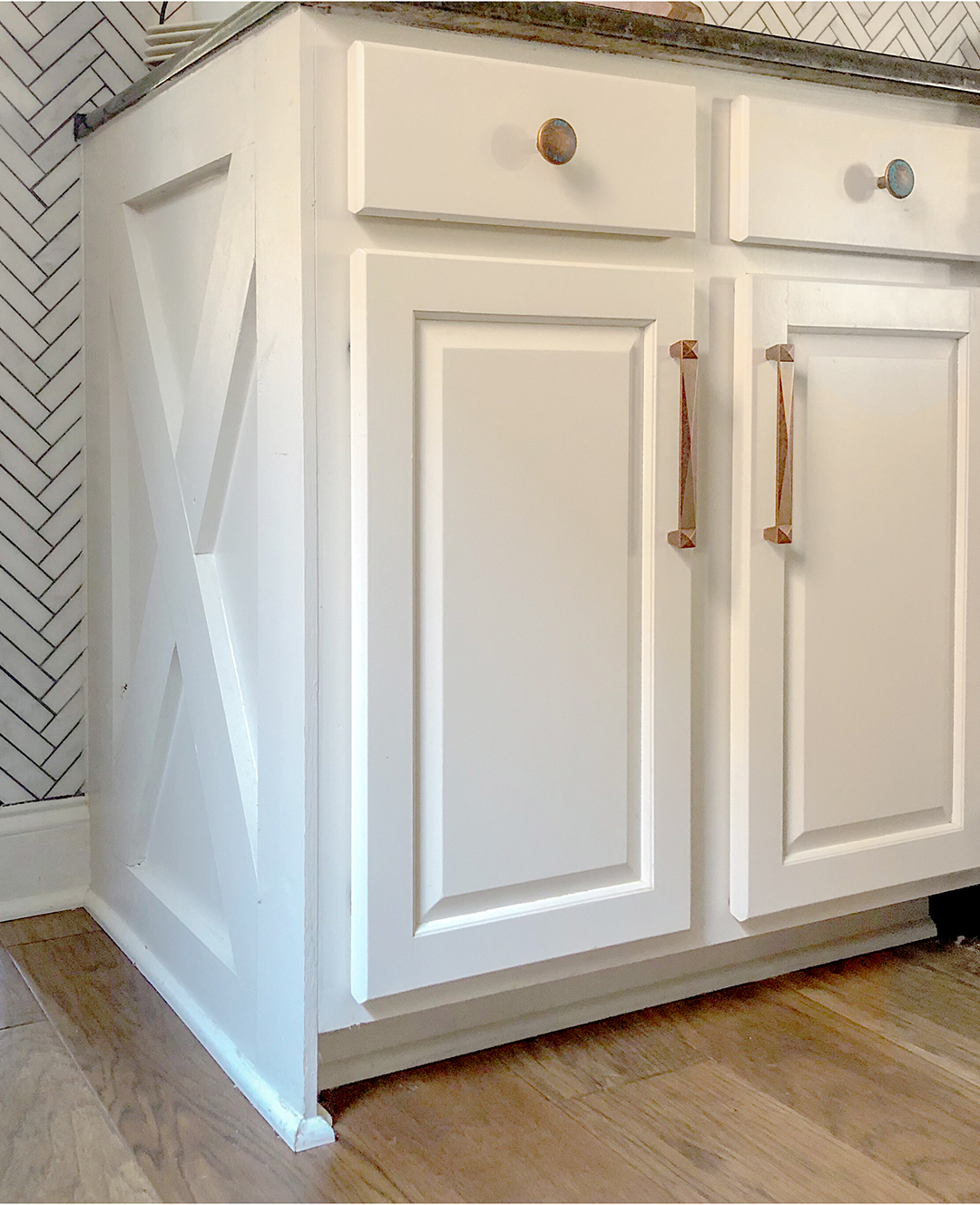 Farmhouse detail on white cabinets with copper pulls