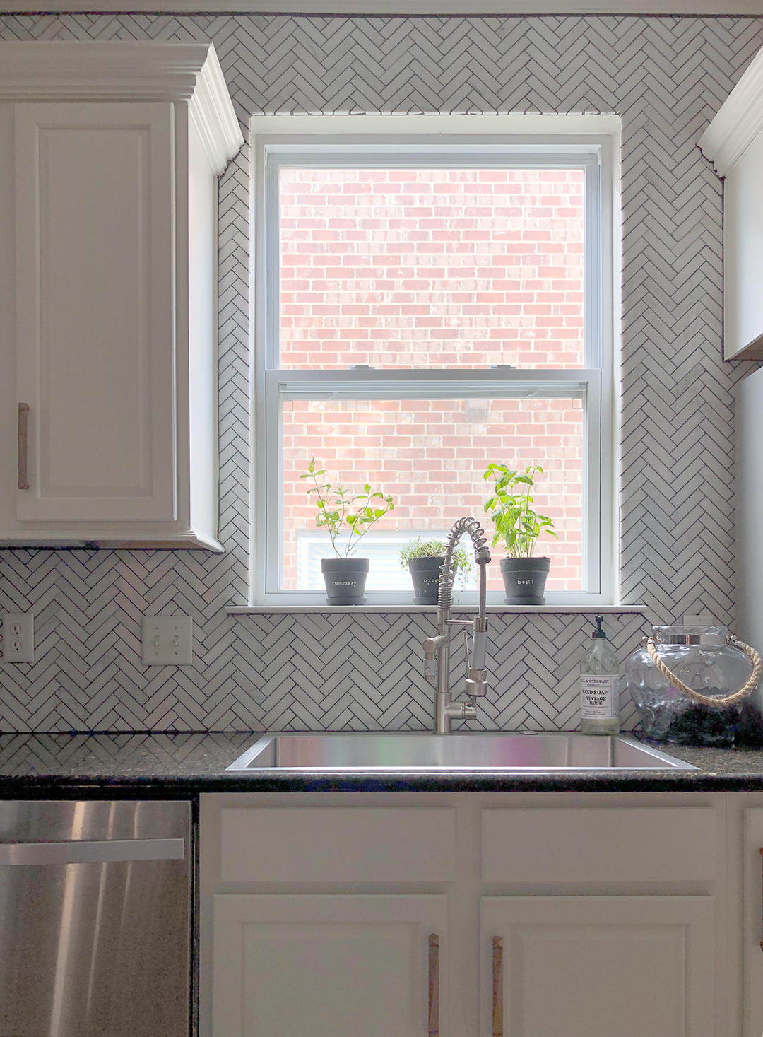 Sarah Miller Kitchen shot of sink with potted herbs, marble herringbone backsplash and dark stone counters
