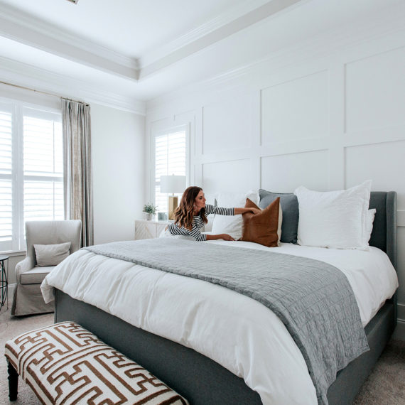 Sarah arranges cognac leather pillows on a white duvet