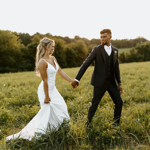 bride and groom walk through field holding hands