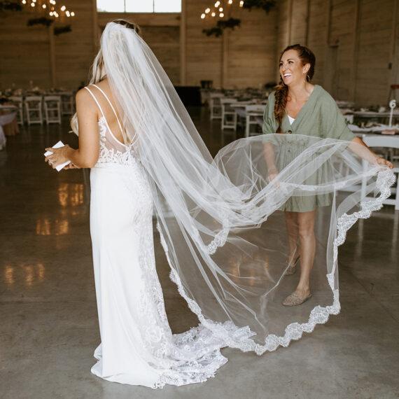 Sarah Miller, wedding planner, adjusts bride's veil