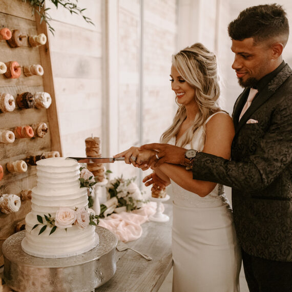 Bride and groom cut cake in front of donut wall